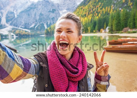 Smiling young woman showing victory gesture while making selfie on lake braies in south tyrol, italy - stock photo