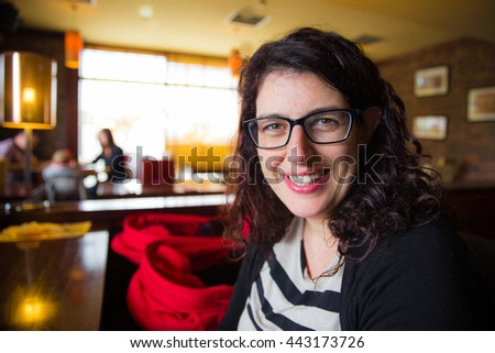 Smiling young woman sitting in a restaurant with her pram next to her - stock photo