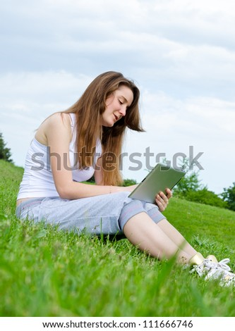 Smiling young woman sitting in the sunshine on grass using a touchscreen tablet