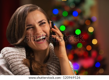 Smiling young woman speaking mobile phone in front of Christmas lights - stock photo