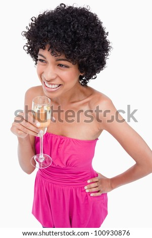 Smiling young woman standing with a hand on her hip and drinking champagne - stock photo