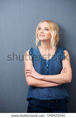 Smiling young woman standing with crossed arms staring up into the air with a smile daydreaming or reminiscing happy memories - stock photo