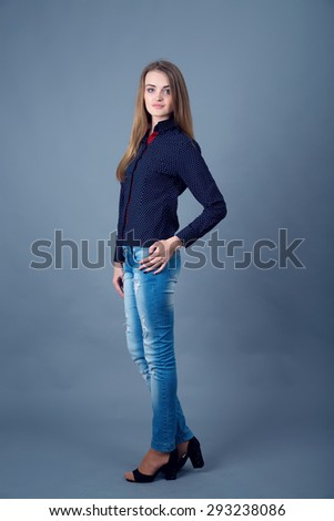 Smiling young woman. Studio portrait on a dark blue background. Portrait of female model with long hair. Ordinary woman, people. Photo model. Portrait of a modern woman.