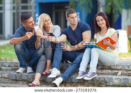 Smiling young woman studying while her friends using mobile phones - stock photo