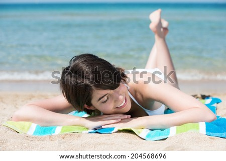 Smiling young woman sunbathing on the beach lying on her towel on the sand at the edge of the surf in the hot summer sun - stock photo