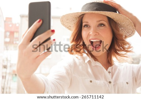 Smiling young woman taking a self portrait on a smartphone - stock photo