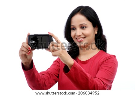 Smiling young woman taking self picture against white background - stock photo