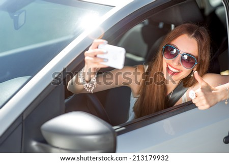 Smiling young woman taking selfie picture with smart phone camera outdoors in car - stock photo