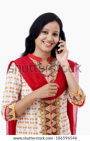 Smiling young woman talking on cell phone against white background - stock photo