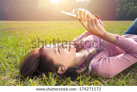 smiling young woman touching cell phone and lying on meadow