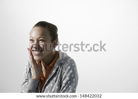 Smiling young woman touching her cheek against gray background - stock photo