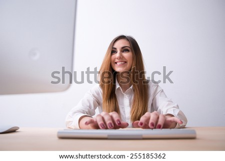 Smiling young woman typing on the keyboard and looking on monitor - stock photo