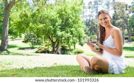 Smiling young woman using her tablet computer on the lawn