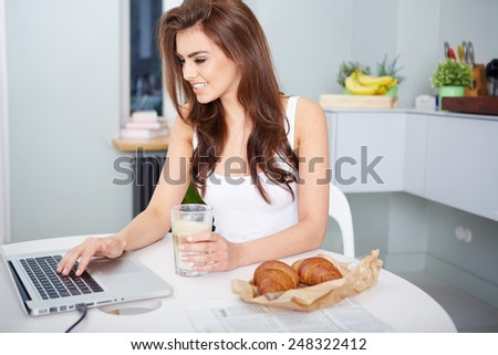Smiling young woman using laptop in the kitchen at home
