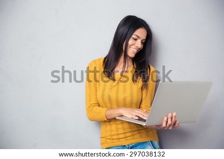 Smiling young woman using laptop over gray background - stock photo