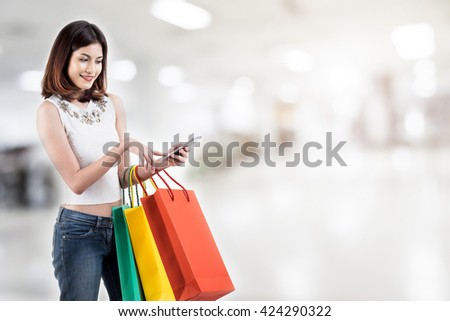 Smiling young woman using smart phone for shopping online over mall background with copy space. Online shopping concept. - stock photo