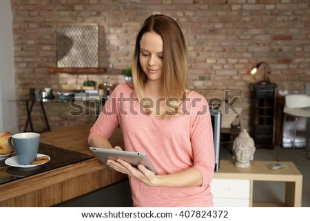 Smiling young woman using tablet computer at home. - stock photo