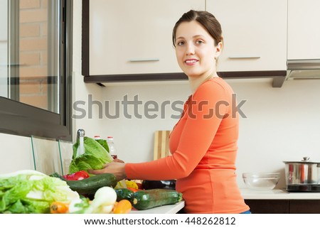 Smiling young woman washing fresh lettuce in sink at home kitchen