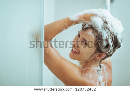 Smiling young woman washing head with shampoo - stock photo