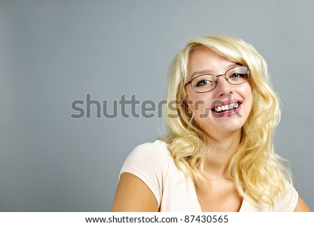 Smiling young woman wearing eyeglasses on grey background - stock photo