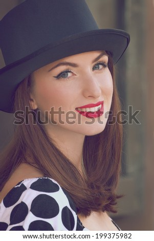 Smiling young woman wearing top hat. Toned image - stock photo