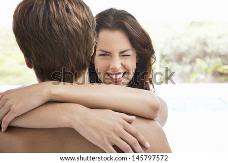Smiling young woman winking while embracing man - stock photo