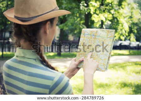 Smiling young woman with a map in the park - stock photo