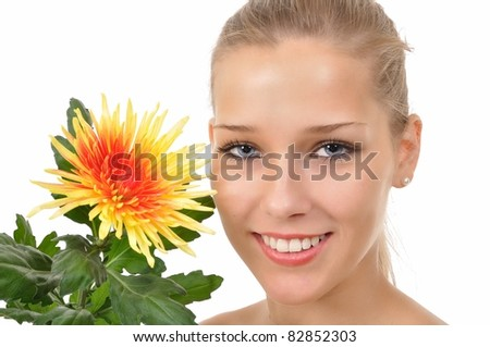 Smiling young woman with blue eyes shows a flower - stock photo