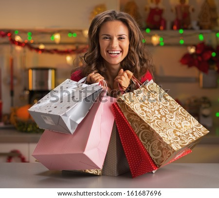 Smiling young woman with christmas shopping bags in christmas decorated kitchen - stock photo