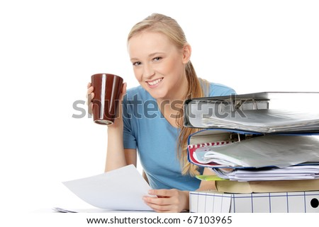 Smiling young woman with coffee cup sitting at the desk, isolated on white - stock photo