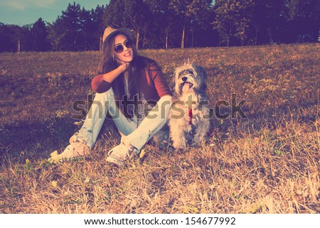 smiling young woman with dog sit on meadow retro colors full body shot - stock photo
