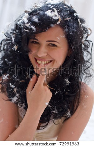 smiling young woman with feathers on a bed