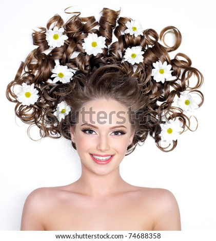 Smiling young woman with flowers in her  long curly hair - white background - stock photo