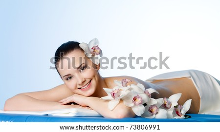 Smiling young woman with flowers resting in the spa salon before massage - colored background - stock photo