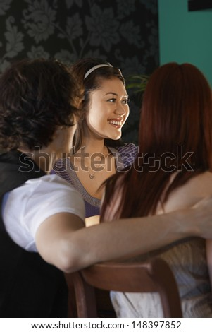 Smiling young woman with friends enjoying dinner party - stock photo