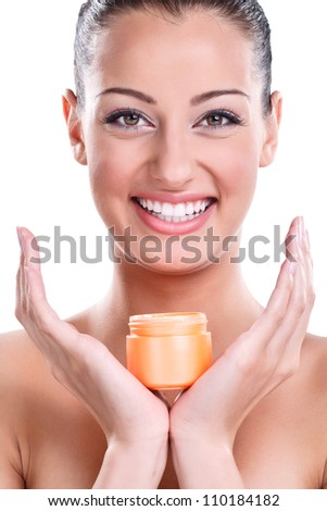 smiling young woman with healthy skin holding cream - stock photo