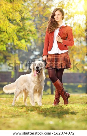 Smiling young woman with her labrador retreiver dog in a park - stock photo