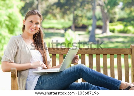 Smiling young woman with her laptop on a park bench