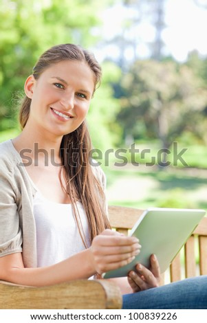 Smiling young woman with her tablet on a park bench - stock photo