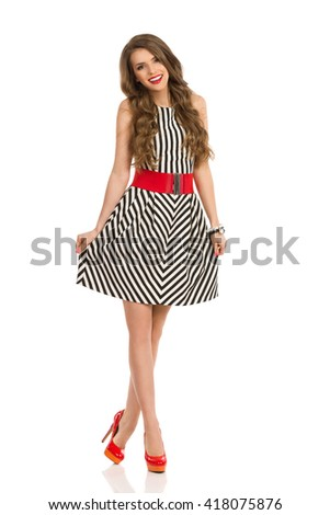Smiling young woman with long brown hair posing in black and white striped dress and high heels. Full length studio shot isolated on white. - stock photo