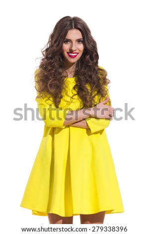 Smiling young woman with long curly hair posing with arms crossed in yellow mini dress. Three quarter length studio shot isolated on white. - stock photo