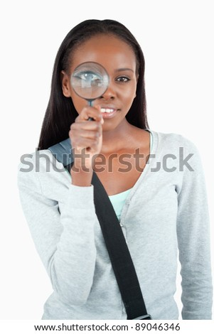 Smiling young woman with magnifier against a white background - stock photo