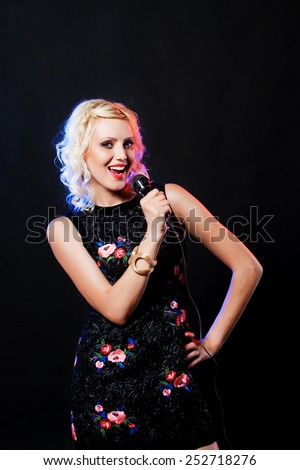Smiling young woman  with microphone singing in karaoke - stock photo