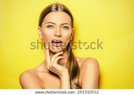 Smiling young woman with natural make-up posing over bright yellow background. Copy space. Cosmetics. Skincare, bodycare.  - stock photo