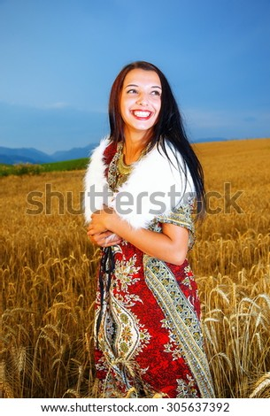 Smiling Young woman with ornamental dress standing on a wheat field with sunset. Natural background. - stock photo