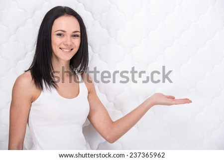 Smiling young woman with orthopedic mattress. Quality mattress. - stock photo