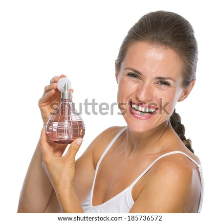 Smiling young woman with perfume bottle - stock photo