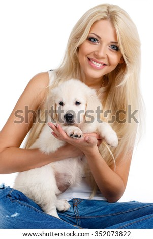 smiling young woman with pet puppy, studio shot. Close up of woman in white sweater with puppy of labrador. Retriever. Love. Puppies. Dogs. Healthcare.