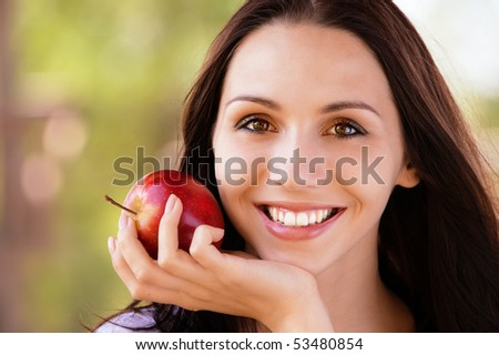 Smiling young woman with red apple - stock photo