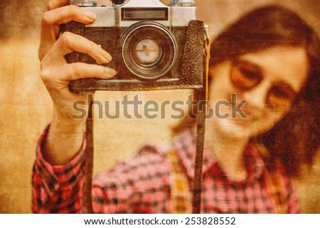 Smiling young woman with retro photo camera, focus on camera. Vintage image - stock photo